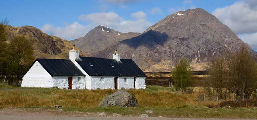 Whitewashed cottage with mountains behind